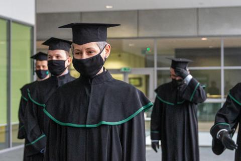 czterech mężczyzn w togach akademickich i w czarnych maseczkach