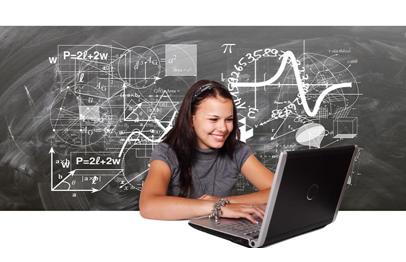Kobieta przed laptopem na tle czarnej, zapisanej tablicy