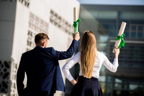 Studenci trzymający w ręku dyplom